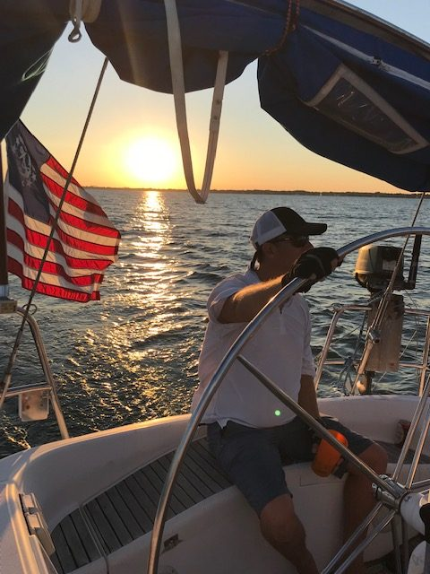 steering boat at sunset